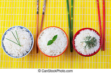 Rice bowls - Three bowls of rice with chopsticks on a yellow...