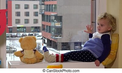 Cute child with best friend teddy bear sitting near window. Snow fall