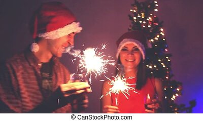 Handsome Man and Beautiful Woman wear Santa cap greeted the new year, lighting sparklers, laughing, kissing and enjoying on a Christmas tree background with bokeh lights.