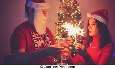 Young handsome man and beautiful woman wear Santa cap greeted the new year, drinking champagne, lighting sparklers, laughing, kissing and enjoying on a Christmas tree background with bokeh lights.