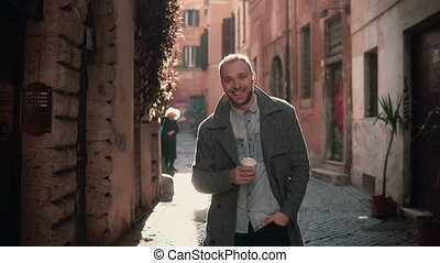 Portrait of young handsome man looking at camera. Happy smiling male standing in morning street, drinking coffee.