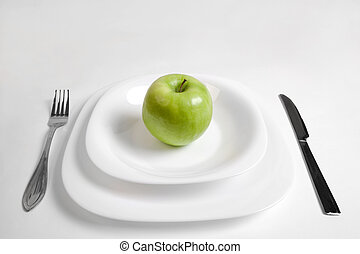 healty food - green apple on a white plate