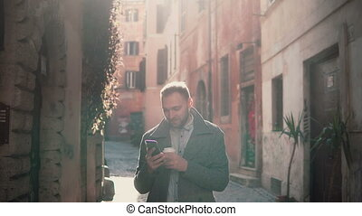 Young smiling man walking in city at morning and using...