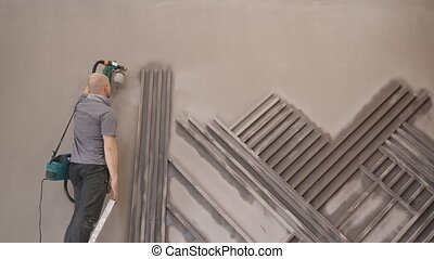 man stands on stairs painting wall with electric paint...