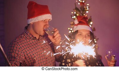 Handsome Man and Beautiful Woman Taking a Selfie with Smarphone wear Santa cap greeted the new year, lighting sparklers, laughing, kissing and enjoying on a Christmas tree background with bokeh lights