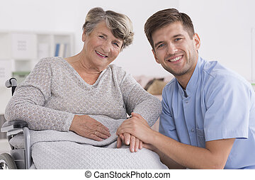 Happy elderly woman with male nurse in retirement home