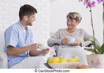 DIsabled elderly woman in inursing home with young...