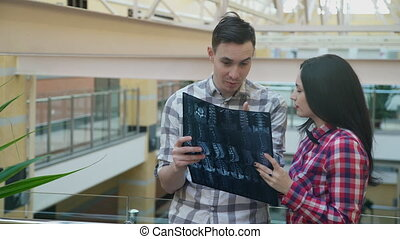 In the hall the young man explains woman picture X-ray of...