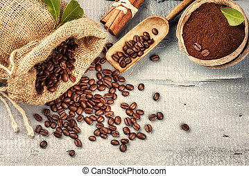 Roasted coffee beans with ground coffee and cinnamon sticks on wooden background