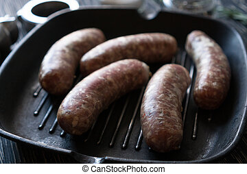 raw sausages on a pan on wooden background