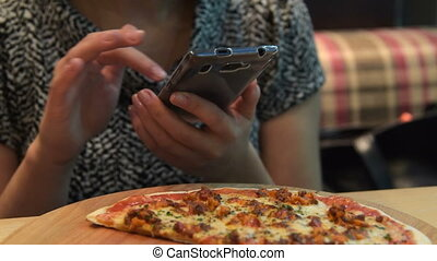 Woman eating pizza and using smart phone - Woman using...