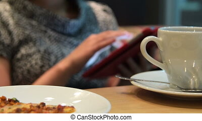 Woman using pad during dinner break - Woman in cafe surfing...