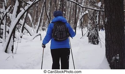 Woman with backpack Cross-Country Skiing Alone in Nature during snowfall in winter in slow motion.