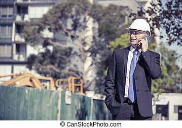 Man architector outdoor at construction area having mobile conve