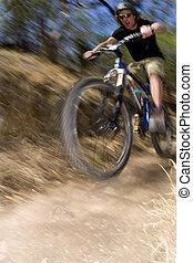 Riding a mountain bike through the bush fast - A stock...