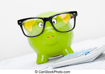 Piggy bank in glasses next to a calculator