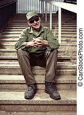 Lazy soldier on sentry duty in city relaxing on stairs -...