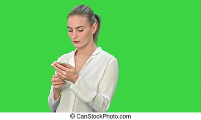 Pensive business woman using mobile cell phone reading message, wear white suit on a Green Screen, Chroma Key.