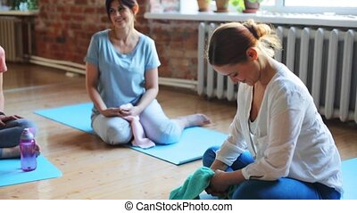 group of women resting on yoga mats in gym