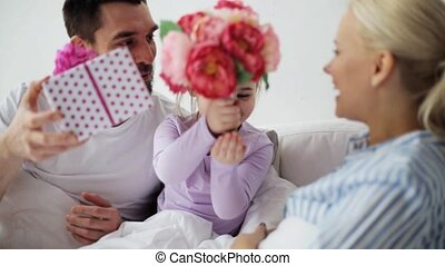 family giving flowers and gift to mother in bed - people,...