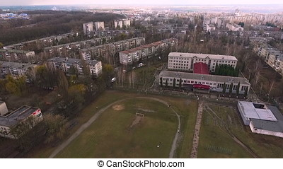 Aerial school and stadium at small town in the spring