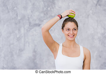 Smiling woman doing yoga pose holding apple on her head.