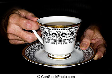 Elderly hands holding a cup of tea - A stock photograph of...