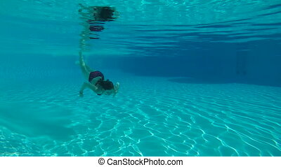 Beauty slowmotion with young woman swimming underwater in swimming pool