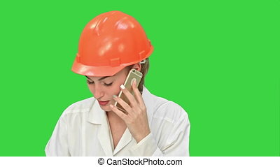 Angry woman construction worker in a hardhat shouting, talking on smartphone on a Green Screen, Chroma Key.