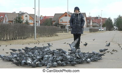 Woman stands next to flocks of pigeons in park - Woman...