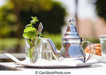 Teapot and glass with mint leaves, Morocco - Image of a...