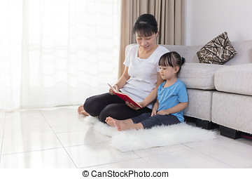 Asian Chinese mother and daughter reading on the floor