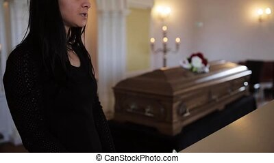 sad woman and coffin at funeral in church