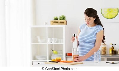 pregnant woman with blender cooking fruits at home - healthy...