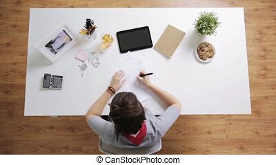 woman with papers and calculator at home office - business,...