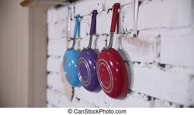 Frying pans on the wall - Multi-colored frying pans hang on...