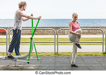 Man exercising on elliptical trainer and woman. - Active...