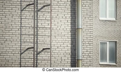 Fire escape on a wall of the brick multi storey building,