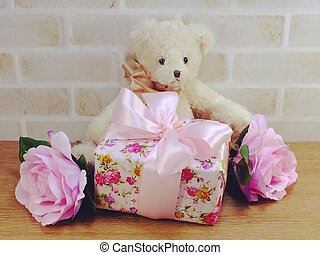 cute teddy bear doll with gift box and flowers with copy space