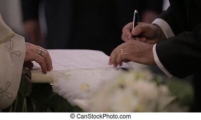The bride and groom put a signature after the wedding in the...