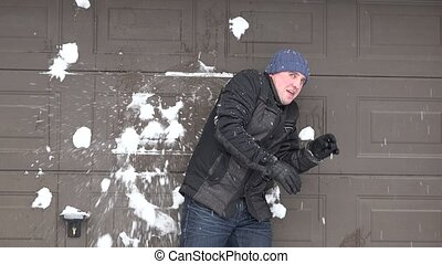 man standing near wall and someone throwing snow balls at...