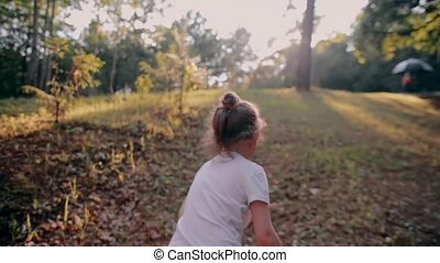 A cheerful little girl running up on a hill in the nature on a sunny summer day. Slow mo, back view