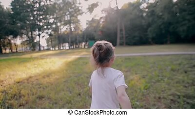 A cheerful little girl runs away from camera in the nature...