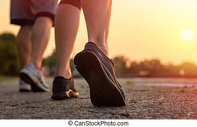 Close-up of a man's legs and a girl in sneakers running at sunset.