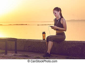 young girl in headphones and with a shaker for a protein...