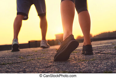 man's legs and a girl in sneakers running at sunset.