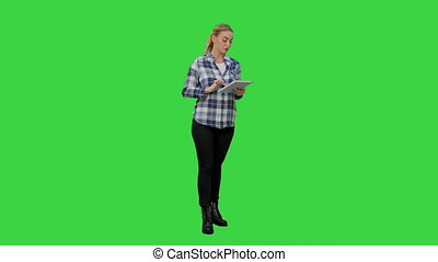 Young woman using reading presentation from a tablet on a Green Screen, Chroma Key.