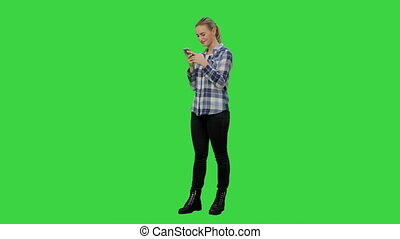 Young pretty blond woman typing on smartphone and smiling on a Green Screen, Chroma Key.