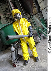 professional in protective uniform, mask, gloves with fire extinguisher in industrial building