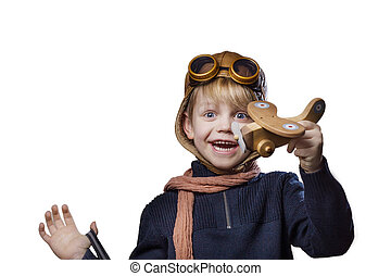 Happy child dressed in pilot hat and glasses. Kid playing with wooden toy airplane. Dream and freedom concept. Retro. Studio portrait isolated over white background